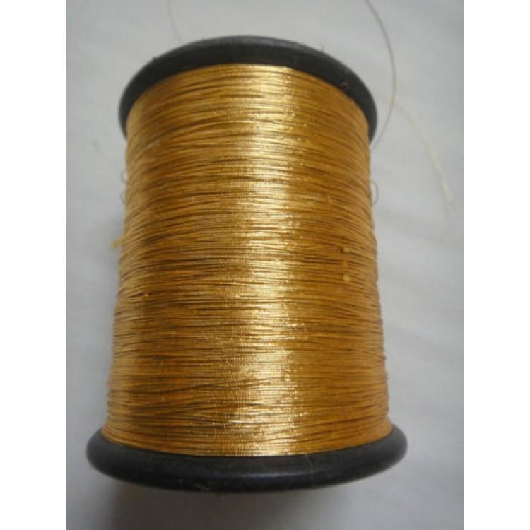 dark gold spool of shiny metallic thread yarn for crochet sewing